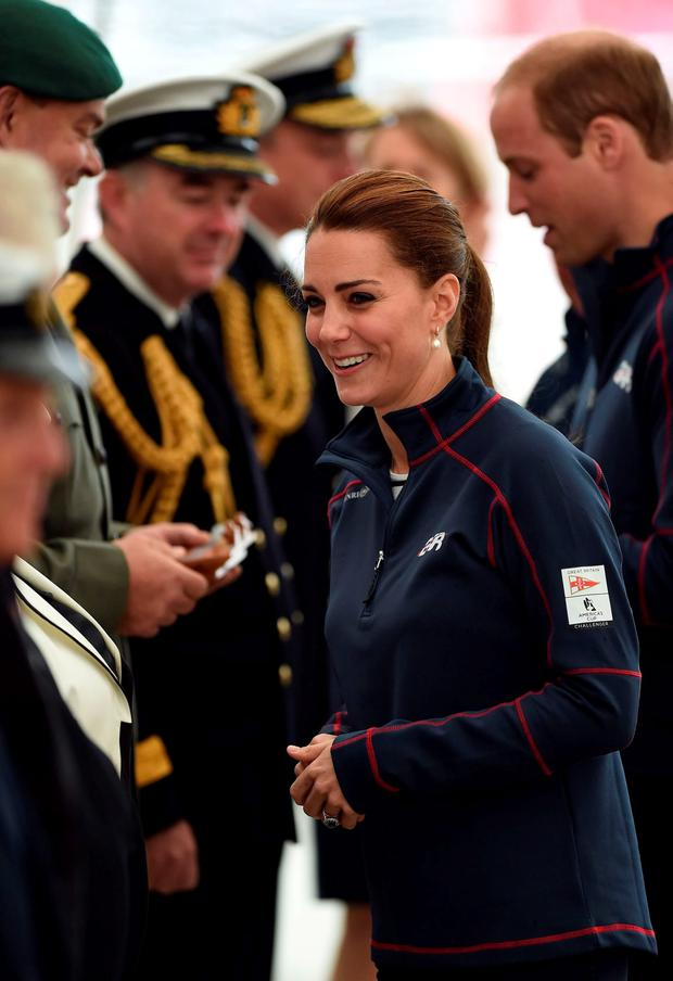 The Duke and Duchess of Cambridge meet guests as they arrive at the team technical areas at the Royal Navy Historic Dockyard, Portsmouth, during a visit on the second day of the opening leg of the America's Cup World Series being staged in waters off Portsmouth. PRESS ASSOCIATION Photo. Picture date: Sunday July 26, 2015. See PA story ROYAL Kate. Photo credit should read: Andrew Matthews/PA Wire
