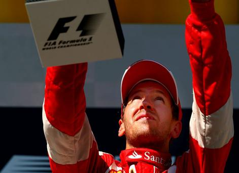 Sebastian Vettel of Germany and Ferrari celebrates with the trophy after winning the Formula One Grand Prix of Hungary at Hungaroring