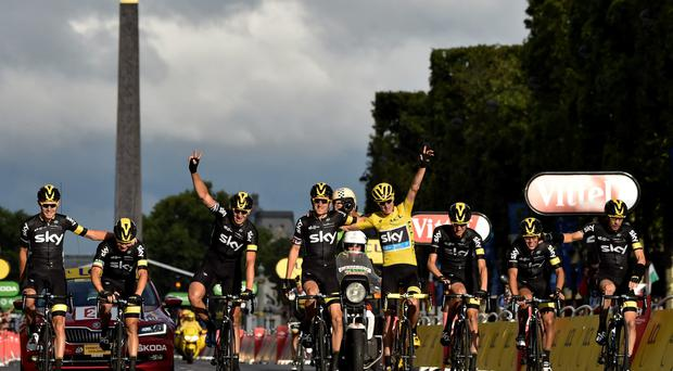 Chris Froome (c), wearing the overall leader's yellow jersey, arrives with his teammates of the Great Britain's Sky cycling team as he crosses the finish line