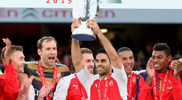 Mikel Arteta, the Arsenal captain raises the trophy after their victory during the Emirates Cup match between Arsenal and VfL Wolfsburg at the Emirates Stadium