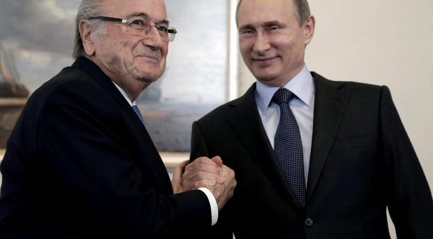 Russian President Vladimir Putin (R) shakes hands with FIFA president Sepp Blatter during a meeting in St. Petersburg
