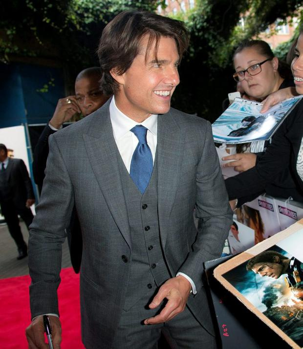 Actor Tom Cruise signs autographs for fans as he arrives for the UK premiere of Mission: Impossible- Rogue Nation
