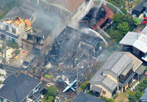 Firefighters investigate the site of the plane crash in the suburbs of Tokyo yesterday, which also set fire to neighbouring houses