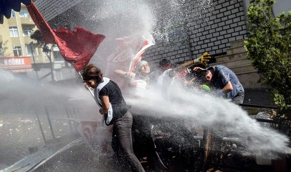Left-wing militants try to protect themselves as Turkish anti-riot police fire water cannon to disperse a demonstration in Istanbul