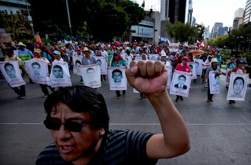 Relatives of the 43 missing students from the Isidro Burgos rural teachers college march holding pictures of their missing loved ones during a protest in Mexico City, Sunday, July 26, 2015. (AP Photo/Marco Ugarte)