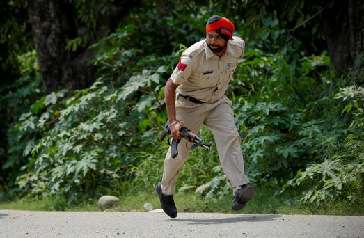 An Indian policeman takes position during a fight in the town of Dinanagar, in the northern state of Punjab, India, Monday, July 27, 2015. (AP Photo/ Channi Anand)