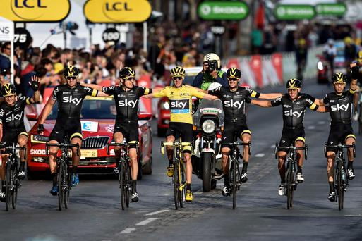 Chris Froome (C), wearing the overall leader's yellow jersey, arrives with his teammates of the Great Britain's Sky cycling team to cross the finish line on the Champs-Elysees avenue at the end of the 109,5 km twenty-first and last stage of the 102nd edition of the Tour de France cycling race on July 26, 2015, between Sevres and Paris. AFP PHOTO / ERIC FEFERBERGERIC FEFERBERG/AFP/Getty Images