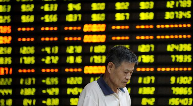 An investor stands in front of an electronic board showing stock information at a brokerage house in Huaibei, Anhui province. Photo: Reuters