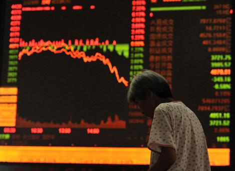An investor stands in front of an electronic board showing stock information at a brokerage house in Fuyang, Anhui province. Photo: Reuters