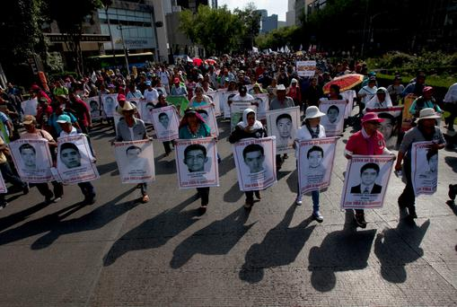 Relatives of the 43 missing students from the Isidro Burgos rural teachers college march holding pictures of their missing loved ones during a protest in Mexico City. Photo: AP