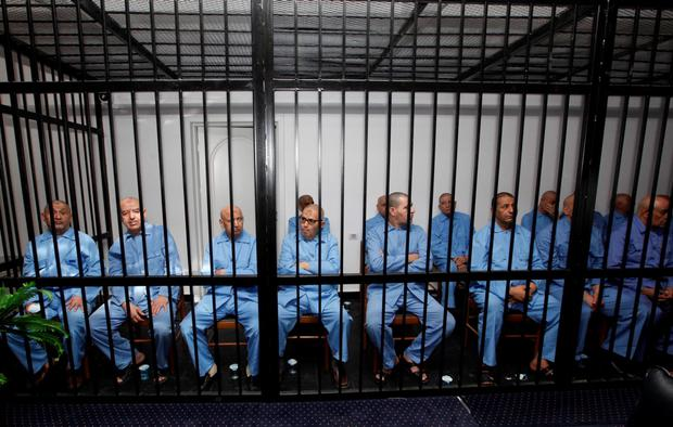 Former Gaddafi regime's officials sit behind bars during a verdict hearing at a courtroom in Tripoli Credit: REUTERS