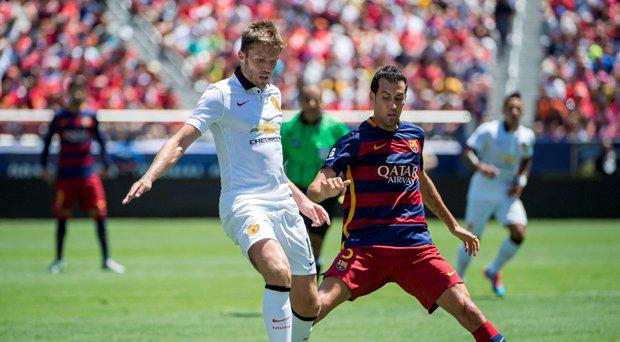 Michael Carrick (L) of Manchester United protects the ball from Sergio Busquets (R) of FC Barcelona during an International Champions Cup match at Levi's Stadium in Santa Clara, California on July 25, 2015