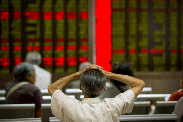 A Chinese investor monitors displays of stock information at a brokerage house in Beijing. Photo: AP