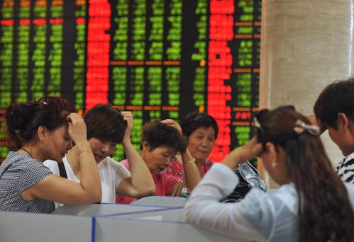 Investors react as they look at computer screens showing stock information at a brokerage house in Fuyang, Anhui province, China, yesterday. Photo: Reuters