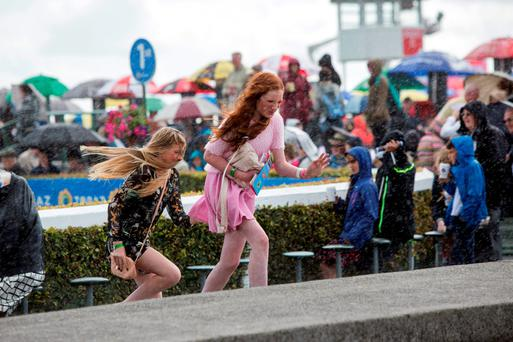 Racegoers run for shelter from the rain on day two 2015 Galway racing festival. Pic:Mark Condren 28.7.2015