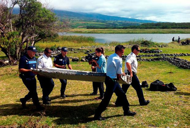 Police carry a piece of debris from an unidentified aircraft washed up on the French Indian Ocean island of La Reunion Credit: Yannick Pitouy