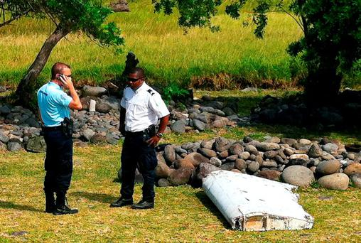 A policeman and a gendarme stand next to a piece of debris from an unidentified aircraft found in the coastal area of Saint-Andre de la Reunion, in the east of the French Indian Ocean island of La Reunion, on July 29, 2015. AFP PHOTO / YANNICK PITONYANNICK PITON/AFP/Getty Images