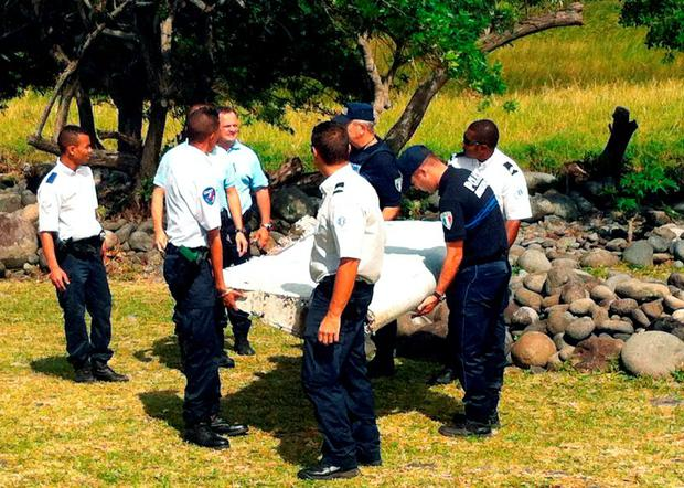 Police and gendarmes carry a piece of debris from an unidentified aircraft found in the coastal area of Saint-Andre de la Reunion, in the east of the French Indian Ocean island of La Reunion