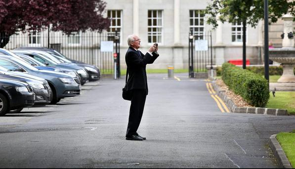 Former Green Party leader John Gormley takes a photo on his phone as he arrives at Leinster House yesterday. Photo: Steve Humphreys.