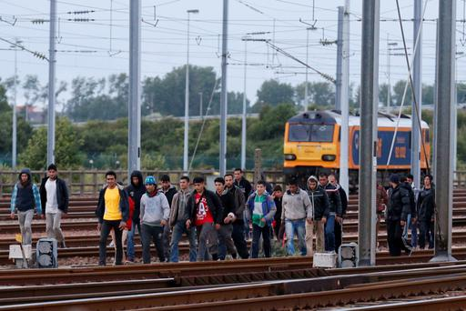 Migrants make their way along train tracks as they attempt to access the Channel Tunnel in Frethun, near Calais. Photo: Reuters