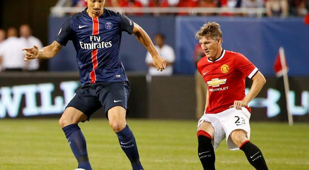 Paris Saint-Germain forward Zlatan Ibrahimovic keeps the ball away from Manchester United's Bastian Schweinsteiger