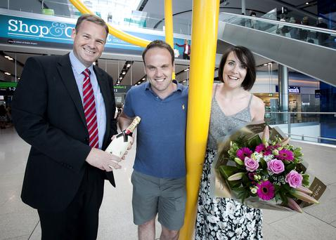 Dublin Airport Head of Operations Gary McLean presents Mark Owen and Lisa Walsh with champagne, flowers and chocolates to mark the fact that Ms Walsh was the two and a half millionth passenger to use Dublin Airport in July.