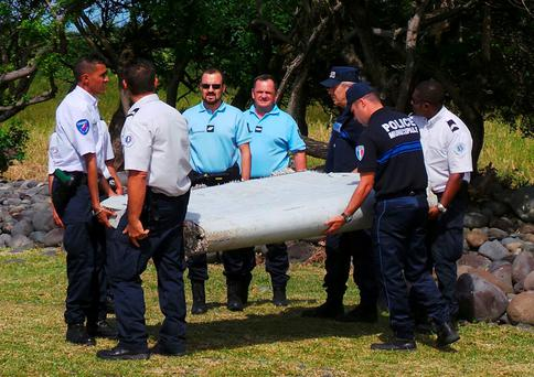 French gendarmes and police carry a large piece of plane debris which was found on the beach in Saint-Andre, on the French Indian Ocean island of La Reunion, July 29, 2015. France's BEA air crash investigation agency said it was examining the debris, in coordination with Malaysian and Australian authorities, to determine whether it came from Malaysia Airlines Flight MH370, which vanished last year in one of the biggest mysteries in aviation history. Picture taken July 29, 2015. REUTERS/Zinfos974/Prisca Bigot