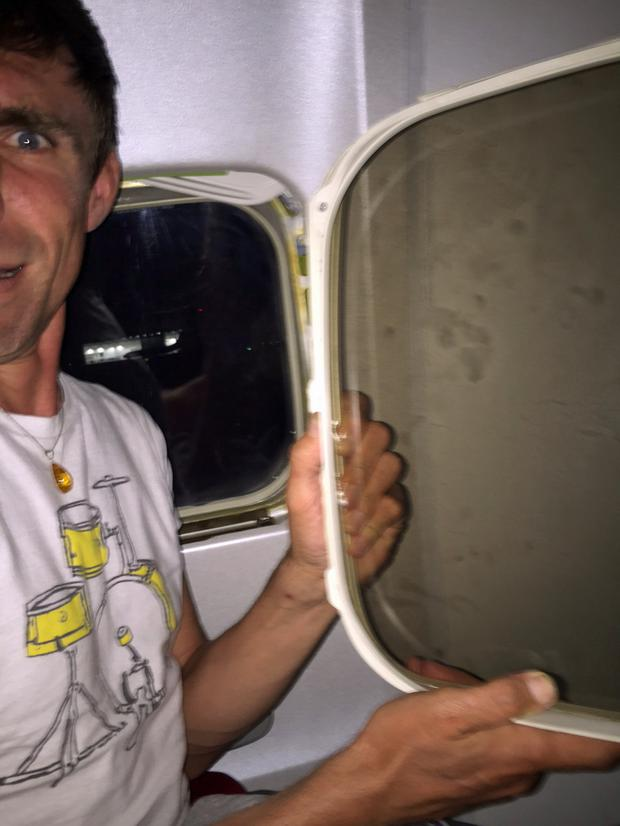 PIC FROM CATERS NEWS - (PICTURED: Laurence holding the window after it fell out ) - A holidaymaker got the shock of his life when a plane window fell into his lap on landing. Laurence Gibson was left traumatised after the window reveal fell on to him as the Ryanair flight touched down at London Stansted around 12.30am on July 26 (SUN). The 37-year-old teaching assistant was returning from a week-long holiday in Gdansk, Poland, with his partner, Matt, when the shocking incident happened. Laurence said: It was the scariest moment of my life. SEE CATERS COPY.