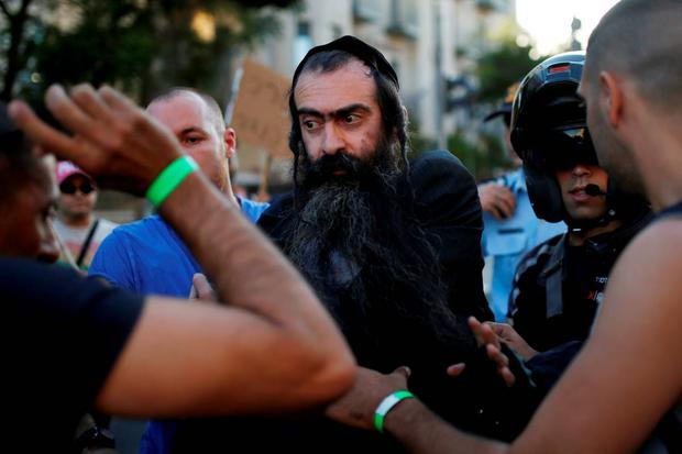 People detain after disarming an Orthodox Jewish assailant, after he stabbed and injured six participants of an annual gay pride parade in Jerusalem on Thursday, police and witnesses said July 30, 2015. REUTERS/Amir Cohen