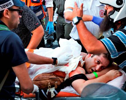 A participant of an annual gay pride parade is treated after an Orthodox Jewish assailant stabbed and injured six participants in Jerusalem on Thursday, police and witnesses said July 30, 2015. REUTERS/Carsten Seibold