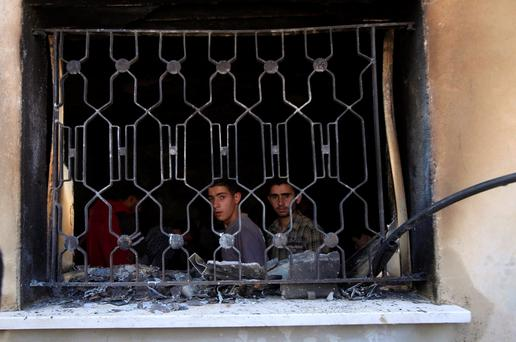 Palestinians look out of a house that had been torched in a suspected attack by Jewish extremists, killing an 18-month-old Palestinian child, injuring a four-year-old brother and both their parents at Kafr Duma village near the West Bank city of Nablus July 31, 2015. REUTERS/Abed Omar Qusini