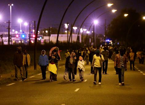Migrants, including young children, are moved away from the perimeter fence of the Eurotunnel site at Coquelles in Calais, as French police make their nightly sweeps of the area Credit: Yui Mok/PA Wire