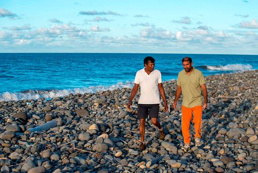 Johnny Begue (R), who found plane debris Wednesday on this beach in Saint-Andre, on the French Indian Ocean island of La Reunion, walks with his friend Andre Tevane, July 30, 2015. REUTERS/Zinfos974/Stringer