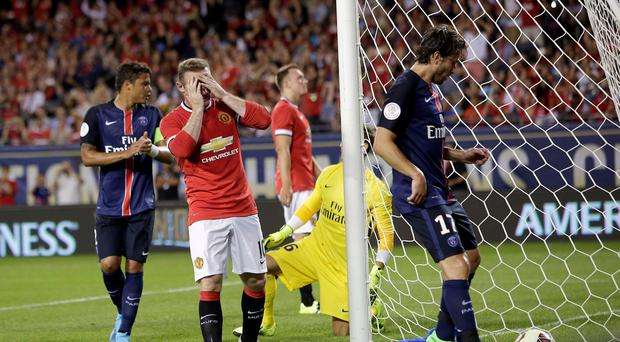 Manchester United forward Wayne Rooney (C) reacts after missing a goal against Paris Saint-Germain