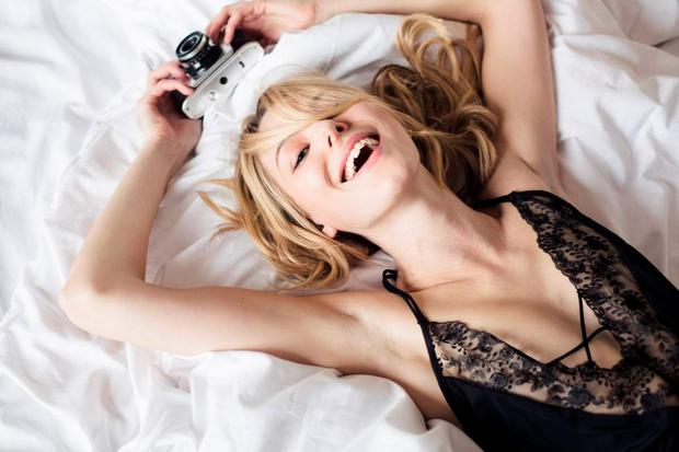 Portrait of smiling young woman wearing black lingerie lying on bed with camera