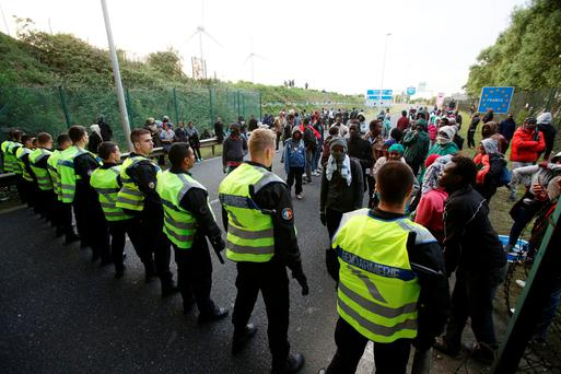 Migrants face a police cordon by the perimeter fence of the Eurotunnel in Calais Credit: Yui Mok/PA Wire