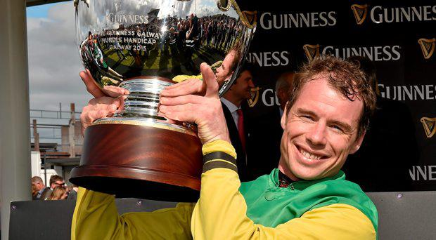 30 July 2015; Denis O'Regan lifts the trophy after winning winning the Guinness Galway Hurdle Handicap on Quick Jack. Galway Racing Festival, Ballybrit, Galway. Picture credit: Cody Glenn / SPORTSFILE