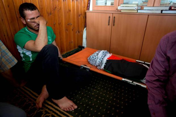 A Palestinian man mourns alongside the body of a one-and-a-half year old boy, Ali Dawabsheh, during his funeral in Duma village near the West Bank city of Nablus, Friday, July 31, 2015. (AP Photo/Majdi Mohammed)