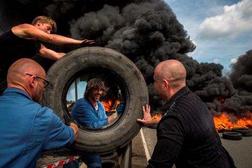 Ferry workers from My Ferry Link burn tyres as they block a key route into Calais as part of a dispute over job losses. Strike action and attempts by migrants to cross the Channel, below, are causing delays in crossings from France into England. Photo: Getty Images