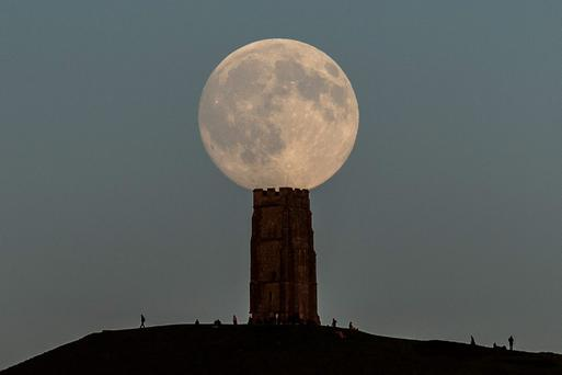 The moon rises over Glastonbury Tor, Somerset, as people gather in anticipation the night before a 'blue moon', which will officially rise on Friday. PRESS ASSOCIATION Photo. Picture date: Thursday July 30, 2015. The term blue moon refers to the second of two full moons appearing in the same calendar month. See PA story SCIENCE Moon. Photo credit should read: Ben Birchall/PA Wire