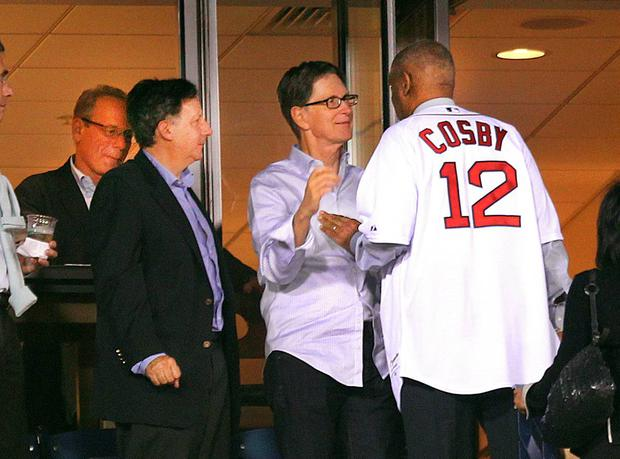 Comedian Bill Cosby greets Boston Red Sox owner John Henry during the game as Larry Lucchino, left, and Tom Werner look on. The Boston Red Sox played the New York Yankees at Fenway Park. (Photo by John Tlumacki/The Boston Globe via Getty Images)
