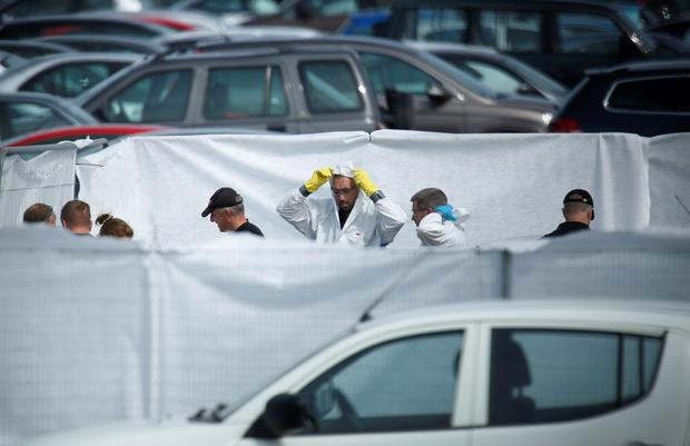 Crash investigors inspect the site of an airplane crash at the British Car Auctions lot next to Blackbushe Airport, near Camberley, in southern Britain August 1, 2015. Reuters/Luke MacGregor