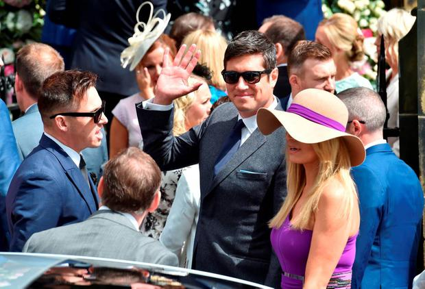 Vernon Kay waves to onlookers as he arrives with his wife Tess Daly to attend the wedding of Declan Donnelly and Ali Astall, at St Michael's Church, Elswick, Newcastle. PRESS ASSOCIATION