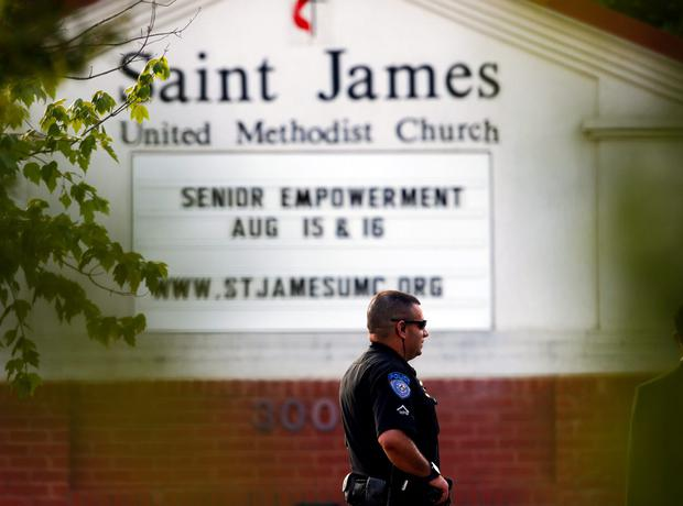 A police officer stands guard at the entrance to St. James United Methodist Church before funeral services for Bobbi Kristina Brown Saturday, Aug. 1, 2015, in Alpharetta, Ga. (AP Photo/John Bazemore)