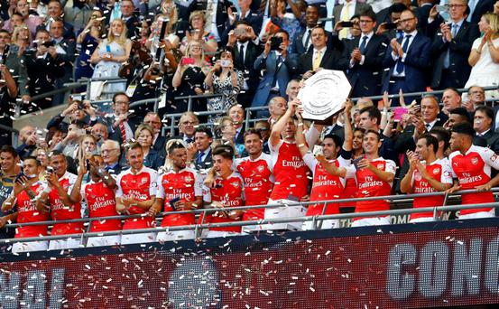 Arsenal's Mikel Arteta and Per Mertesacker lift the trophy after winning the FA Community Shield