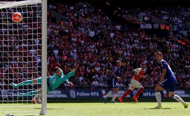 Chelsea's goalkeeper Thibaut Courtois cannot stop the shot from Arsenal midfielder Alex Oxlade-Chamberlain