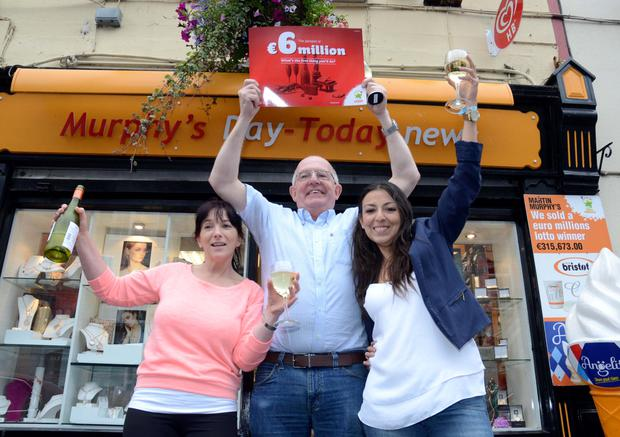 Staff at Murphys in Ballinrobe where the €6m lottery ticket was sold. From left to right, Rosie O'Connor, Martin Murphy, owner, and Dolce McTigue celebrate outside their shop.