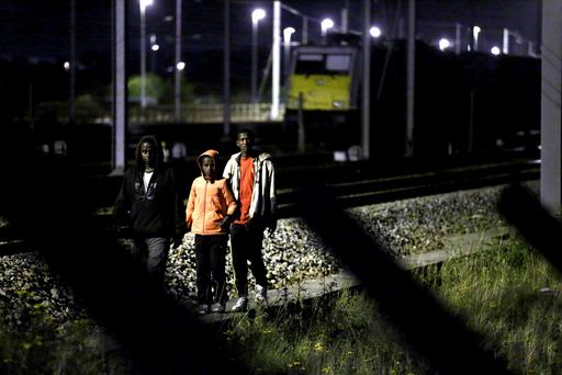 Migrants make their way along train tracks as they attempt to access the Channel Tunnel in Frethun, near Calais, France, August 2, 2015. Reuters/Pascal Rossignol