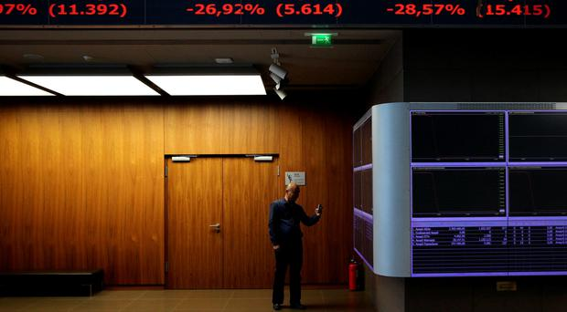 A journalist takes pictures of the electronic boards displaying stock prices in the reception hall in Athens stock exchange, Greece August 3, 2015. REUTERS/Yiannis Kourtoglou