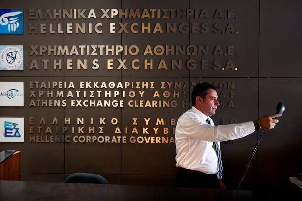 An employee hands over the phone at the entrance of the Athens Stock Exchange, Greece, August 3, 2015. Greece's stock market plunged nearly 23 percent on Monday when it opened after a five-week shutdown brought on by fears the country was about to be dumped from the euro zone. REUTERS/Yiannis Kourtoglou